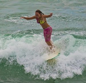 Learn to surf like the smiling girl on a wave