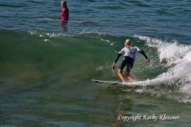 Stephanie Gilmore riding a small wave while Bethany Hamilton looks on.
